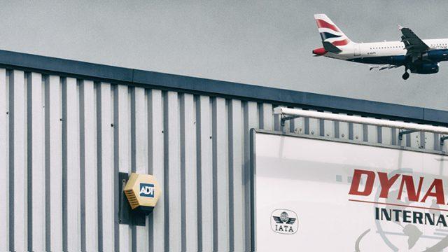 Freight aircraft flying over hangar