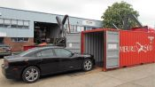 Car being loaded into shipping container