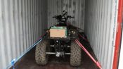 Quad bike strapped inside container